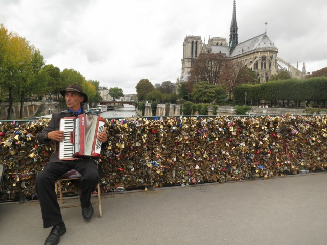 Typical French street musician at the love-lock bridge across Notre Dame